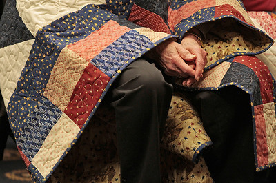 Kyle Grillot - kgrillot@shawmedia.com   Donald McLeod of Huntley sits with his quilt draped over his shoulders after it was presented to him during the Quilts of Valor presentation Tuesday at American Community Bank in Huntley. The national organization has awarded over 96,000 quilts since 2003. The bank has donated their basement for the group to use on the first Tuesday of every month. Local veterans from many wars were awarded the hand-made quilts Tuesday in Huntley, and there is an application process for other local veterans to receive the award.