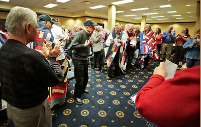 Kyle Grillot - kgrillot@shawmedia.com   World War II Army veteran BIll O'Connell (center left) reacts as the crowd stands to applaud him during the Quilts of Valor presentation Tuesday at American Community Bank in Huntley. The national organization has awarded over 96,000 quilts since 2003. The bank has donated their basement for the group to use on the first Tuesday of every month. Local veterans from many wars were awarded the hand-made quilts Tuesday in Huntley, and there is an application process for other local veterans to receive the award.