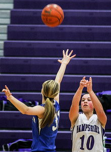 Sarah Nader- snader@shawmedia.com Hampshire's Becky Dumoulin shoots over Woodstock's Dakota Brand during the second quarter of Wednesday's game in Hampshire February 5, 2014. Hampshire defeated Woodstock, 58-36.
