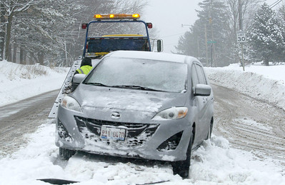 H. Rick Bamman - hbamman@shawmedia.com A tow truck operator works to remove a car stuck in the snow on Highland Aveenue at Algonquin Rd.  Wednesday, Feb. 5, 2014.