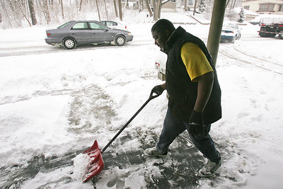 H. Rick Bamman - hbamman@shawmedia.com Algonquin resident Quintan Lightfoot clears snow from his porch as traffic on Rt. 31 crawls by Wednesday, Feb. 5, 2014.