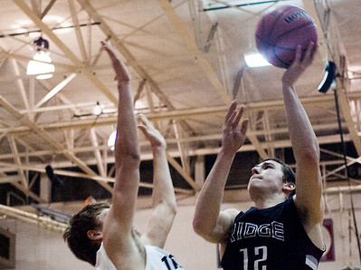 Kyle Grillot - kgrillot@shawmedia.com   Prairie Ridge senior Steven Ticknor puts up a shot under pressure from Cary-Grove junior Jason Gregoire during the third quarter of the boys basketball Friday in Cary. Cary-Grove beat Prairie Ridge, 47-38.