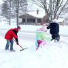 Brian Post shovels his Geneva driveway as his children, Allie, 2, and Brennan, 5, play on a giant mound of snow Wednesday morning. Four inches of snow was reported in Geneva from Tuesday night into Wednesday morning.
