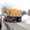 A snow plow drops salt along Wilson Street in Batavia Thursday.