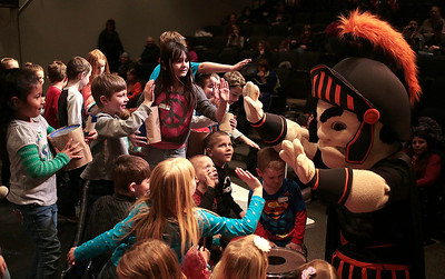 Kyle Grillot - kgrillot@shawmedia.com   Children rush to high five Leonidas, the McHenry mascot, during the McHenry High School's second annual Children's Music Day Saturday, February 8, 2014. During the event, 5 to 10-year olds learn about various instruments, musical composition and conducting.