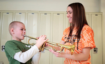 Kyle Grillot - kgrillot@shawmedia.com   McHenry senior Jessica Schwartz helps Thomas Burton, 8, of McHenry try to play a trumpet during the McHenry High School's second annual Children's Music Day Saturday, February 8, 2014. During the event, 5 to 10-year olds learn about various instruments, musical composition and conducting.
