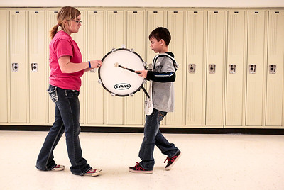 Kyle Grillot - kgrillot@shawmedia.com   McHenry junior Shannon Reel (left) helps students learn to walk while drumming during the McHenry High School's second annual Children's Music Day Saturday, February 8, 2014. During the event, 5 to 10-year olds learn about various instruments, musical composition and conducting.