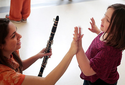 Kyle Grillot - kgrillot@shawmedia.com   McHenry senior Jessica Schwartz high fives Serenity Giles, 6, of McHenry during the McHenry High School's second annual Children's Music Day Saturday, February 8, 2014. During the event, 5 to 10-year olds learn about various instruments, musical composition and conducting.