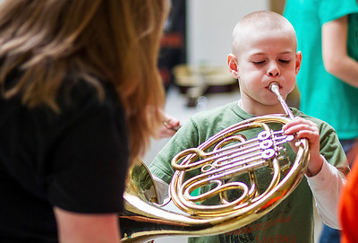 Kyle Grillot - kgrillot@shawmedia.com   Thomas Burton, 8, of McHenry tries out a french horn during the McHenry High School's second annual Children's Music Day Saturday, February 8, 2014. During the event, 5 to 10-year olds learn about various instruments, musical composition and conducting.
