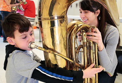 Kyle Grillot - kgrillot@shawmedia.com   McHenry junior Caylin Kaunas watches as chipdren try out the tuba during the McHenry High School's second annual Children's Music Day Saturday, February 8, 2014. During the event, 5 to 10-year olds learn about various instruments, musical composition and conducting.