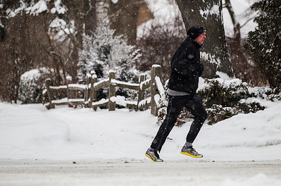 Kyle Grillot - kgrillot@shawmedia.com   A runner turns onto South Walkup Avenue as snow falls Saturday, Janurary 8, 2014. Around 3 inches of snow is expected Saturday and temperatures are expected to reach 20 degrees below zero with wind chills on Sunday and Monday.