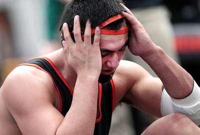 Kyle Grillot - kgrillot@shawmedia.com   McHenry's Luis Hernandez adjusts his head gear after winning a championship semifinal during the 3A Individual Regional Wrestling meet at McHenry High School Saturday, January 8, 2014. Hernandez won the match to advance to the championship round.