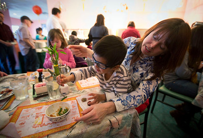 Teri Altpeter, from Huntley, helps her adopted son Zane, 5, with lunch  at the Green Garden Restaurant Sunday, February 9, 2014 in Woodstock. Families who have adopted children from China gather to celebrate Chinese New Year during the annual event started by Rick and Ellen Bellairs of Woodstock.  John Konstantaras Photo for the Northwest Herald