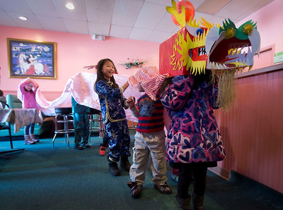 Gina Scichowski, 8 from Spring Grove, peaks out from under a dragon as kids get ready for a dragon dance through the Green Garden Restaurant Sunday, February 9, 2014 in Woodstock. Families who have adopted children from China gather to celebrate Chinese New Year during the annual event started by Rick and Ellen Bellairs of Woodstock.  John Konstantaras Photo for the Northwest Herald