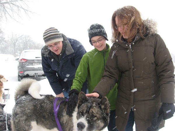 Geneva residents Louis Caballero (from left), Samuel Caballero and Anne Caballero pet Ezra, an Akita breed, on Saturday outside the Hickory Knolls Discovery Center in St. Charles. Ezra is part of the Free Spirit Siberian Rescue Sled Demo Team.