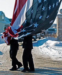 Kyle Grillot - kgrillot@shawmedia.com   Firefighters lower the American flag that was draped between two fire trucks on Raffel Road. The visitation was held at the Woodstock Assembly of God Church, and the procession traveled by each of three Woodstock fire stations. Wurtz ended his battle with cancer yesterday afternoon while surrounded by family and friends. Mike is survived by his wife, three daughters and two step-children.