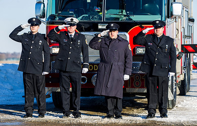 Kyle Grillot - kgrillot@shawmedia.com   With a two fire trucks draping an American flag over Raffel road, Woodstock firefighters stand at attention as cars pass by during the funeral procession for Michael W. Wurtz, 47, a Woodstock firefighter.  The visitation was held at the Woodstock Assembly of God Church, and the procession traveled by each of three Woodstock fire stations. Wurtz ended his battle with cancer yesterday afternoon while surrounded by family and friends. Mike is survived by his wife, three daughters and two step-children.