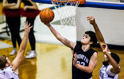 Kyle Grillot - kgrillot@shawmedia.com   Woodstock North's Drake Creighton (23) puts up a shot under pressure from Woodstock's Damian Stoneking (right) and Ryan Princer during the first quarter of the boys basketball game Wednesday in Woodstock. Woodstock North beat Woodstock, 61-58.