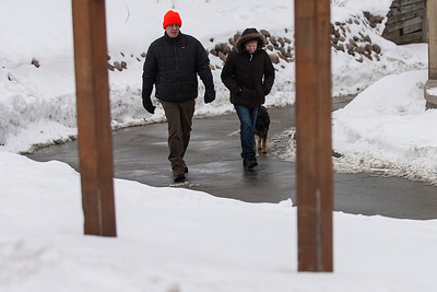 Kyle Grillot - kgrillot@shawmedia.com   Greg Adams and Margie Wood both of Woodstock walk their dog Buddy towards the parking lot after hiking at Veterans Acres Park Thursday in Crystal Lake.