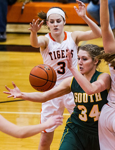 Kyle Grillot - kgrillot@shawmedia.com   Crystal Lake South senior Sara Mickow goes grabs a loose ball under pressure from three Crystal Lake Central players including senior Eveyln Youel (3) during the third quarter of the girls basketball game Friday in Crystal Lake. Crystal Lake South beat Crystal Lake Central, 51-42.