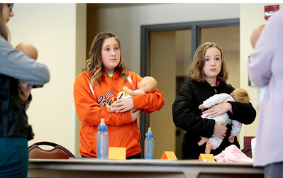 Kyle Grillot - kgrillot@shawmedia.com  Instructor Nancy Jagielski (right) shows Ally Hendrickson, 11, (from left) Hailey Carlson, 11, and Jessi Hyde, 11, how to hold an infant during the Safe Sitter Babysitting Training Course Saturday at the Cary Community Center. The course, taught 3 weekends out of the month at various park districts, offers children ages 11-15 to learn the skills necessary for safe childcare. Some of the topics covered include ethics, safety, first aid, feeding infants, allergies, emergencies, ethics, and behavior management. A babysitting manual and completion card are included with the course.