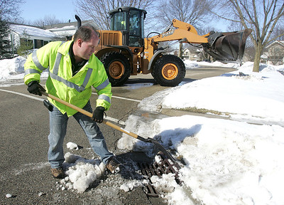 H. Rick Bamman - hbamman@shawmedia.com  Crystal Lake Supervisor of Streets Jim Veugeler (cq) clears snow from a storm drain as maintenance worker Dave Shine operates a front end loader near the intersection of Sarasota Lane and Colony Drive in Crytal Lake Wednesday, Feb 18, 2014. The area is bracing for rain, possibly mixed with snow and freezing rain before 9 a.m. on Thursday.