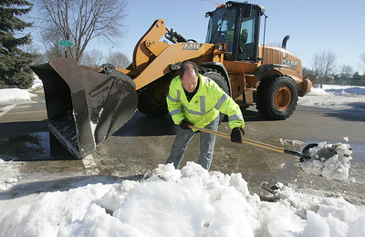 H. Rick Bamman - hbamman@shawmedia.com  Crystal Lake Supervisor of Streets Jim Veugeler (cq) clears snow from a storm drain as maintenance worker Dave Shine operates a front end loader near the intersection of Sarasota Lane and Colony Drive in Crytal Lake Wednesday, Feb 18, 2014.