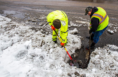 "Kyle Grillot - kgrillot@shawmedia.com   Algonquin Public Works employees Brad McFeggan and Frank Sedivy work to clear drains along Harrison Street Thursday, February 20, 2014. ""Pretty much everyone in the public works is out right now,"" said McFeggan. The National Weather Service has issued a flood advisory for much of northeastern Illinois, including portions of southern McHenry County."