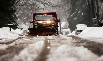 Kyle Grillot - kgrillot@shawmedia.com   A Crystal Lake Public Works employee clears a mixture of snow and rain from Edgewood Road Thursday, February 20, 2014. The National Weather Service has issued a flood advisory for much of northeastern Illinois, including portions of southern McHenry County.