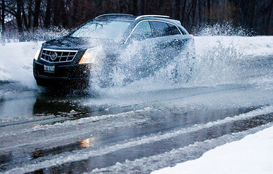 Kyle Grillot - kgrillot@shawmedia.com   A motorist drives through wet snowy conditions along Birch Lane in Fox River Grove Thursday, February 20, 2014. The National Weather Service has issued a flood advisory for much of northeastern Illinois, including portions of southern McHenry County.