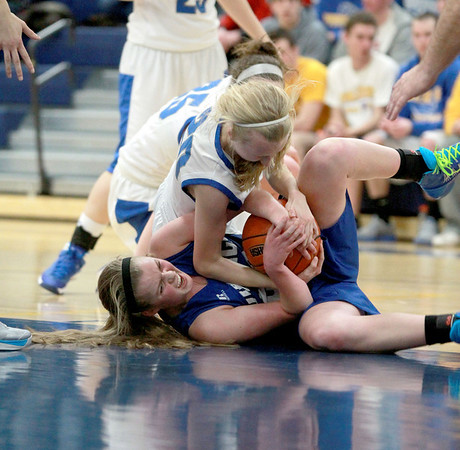 Geneva's Courtney Reynolds (bottom) battles Wheaton North's Abby Tiesman  during their Wheaton North Regional game Thursday night.