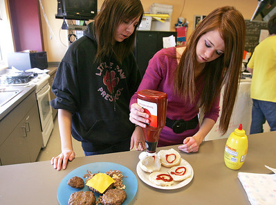 H. Rick Bamman - hbamman@shawmedia.com  Prairie Ridge High School's commercial food students Sonya Quinton and Brooke Bennett prepare a spiced burger during a recent class. Duke's Ale House and Prairie Ridge High School's commercial foods and marketing classes have teamed up to create Duke's special menu for April.