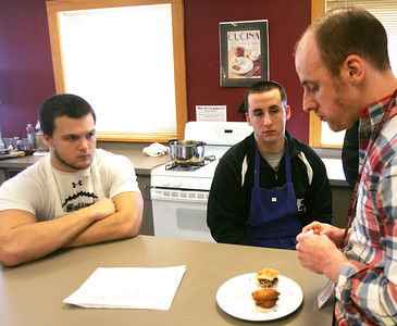 H. Rick Bamman - hbamman@shawmedia.com  Prairie Ridge High School's commercial food students Colin Leverenz (left) and Oliver Kremer wait for feedback from Duke's general manager and head chef Zak Dolezal (right) during a taste test sesson. The students prepared a spiced burger and a Monte Cristo sandwich.
