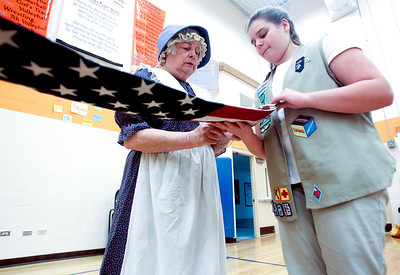 Sarah Nader- snader@shawmedia.com Marcia Flanagan (led) of Woodstock teaches Caitlyn Stelston, 15, of Crystal Lake how to fold a flag during an event hosted by the Kshwaukee Trail chapter of Daughters of the American Revolution at Hannah Beardsley Middle School in Crystal Lake Saturday, February 22, 2014.  Girl Scouts learned about historical flags, flag etiquette, conducting a flag ceremony and the history of the American flag during the event.
