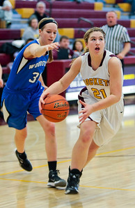 Michelle LaVigne/ For Shaw Media Richmond-Burton's Jessica Guenther (21) dodges Woodstock's Dakota Brand (31) as she heads for the basket during the regional girls basketball final in Richmond on Saturday, February 22, 2014.