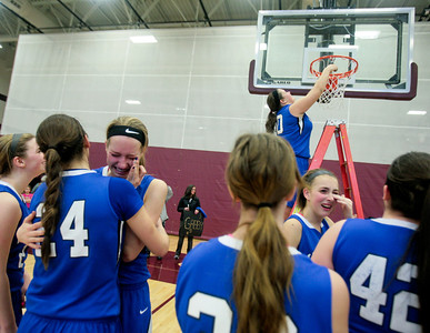 Michelle LaVigne/ For Shaw Media Woodstock's Morgan Kunzie (32) hugs teammate Selena Juarez (24) while Amber Roberts (50) takes her turn at cutting a section of net after winning the girls basketball final in Richmond on Saturday, February 22, 2104.