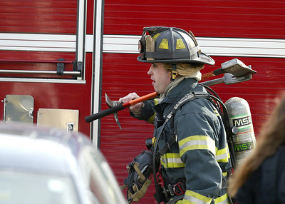 A firefighter carries equipment to the staging area at the Randall Village Condominium complex in Crystal Lake.  H. Rick Bamman - hbamman@shawmedia.com