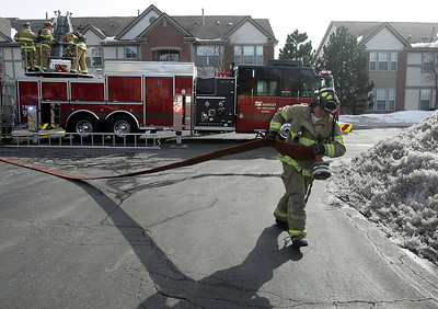 A firefighter drags a hose to a hydrant as crews battle a fire at the Randall Village Condominium complex at 1637 Carlemont Drive in Crystal Lake.  H. Rick Bamman - hbamman@shawmedia.com