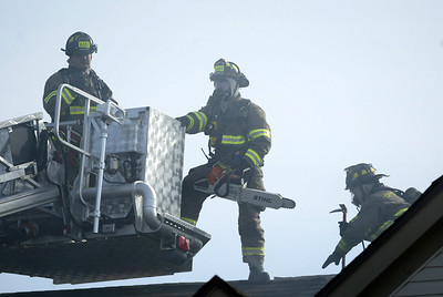 Firefighters prepare to vent the roof during a structure fire at the Randall Village Condominium complex at 1637 Carlemont Drive in Crystal Lake. H. Rick Bamman - hbamman@shawmedia.com
