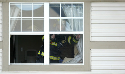A firefighter removes a screen from one of the second floor apartments after a fire broke out at the Randall Village Condominium complex in Crystal Lake Monday, Feb. 24, 2014. H. Rick Bamman - hbamman@shawmedia.com