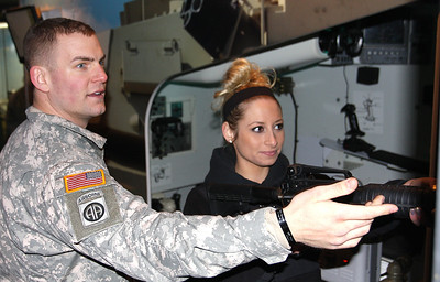 Crystal Lake Recruiting Center Srgt. Thomas Kolanko shows Crystal Lake South student Megan Avella, 18, how to use the shooting simulator aboard the Adventure Semi 1 truck. (Jim Dallke - jdallke@shawmedia.com)