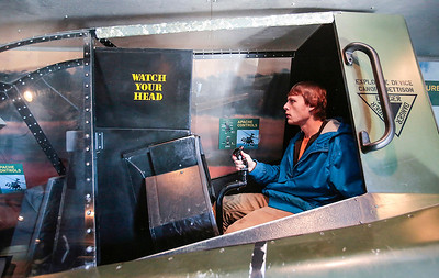 Kyle Grillot - kgrillot@shawmedia.com   Crystal Lake South senior Tyler Anderson test out an an apache helicopter simulator inside the Adventure Semi 1 truck Wednesday in Crystal Lake. There are six Adventure Semi's that travel the United States, giving students a chance to simulate experiences, and find information on the various opportunities within the Army. After the Adventure 1 truck spent the day at Crystal Lake South, it plans to visit Woodstock North High School on Thursday and Cary-Grove High School on Friday.