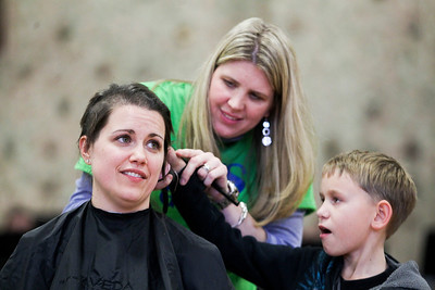 Sarah Nader- snader@shawmedia.com Special ed teacher Tara Busa (left) has her head shaved by Erica Sarna and Lucas Kreinikerm 12, of Spring Grove during  Nippersink Middle School's  St. Baldrick's Day event in Richmond during an all-school assembly Wednesday, February 26, 2014. Students and staff purchased raffle ticket for the chance to shave a teacher head. Busa raised $3,650 for childhood cancer research.