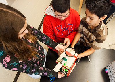 Kyle Grillot - kgrillot@shawmedia.com   Creekside Middle School seventh graders Natalie VanHoorn, (from left) Alexis Pagaza and Brian Ayala put the finishing touches on their microscope they made in Todd Clements Biology class Thursday in Woodstock. As part of the exercise to encourage engineering in the classroom, students were asked to design a magnifying glass out of a box of materials including a pipe, wood, two magnifying glasses, tape, and two flashlights.