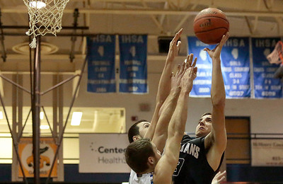 Kyle Grillot - kgrillot@shawmedia.com   Cary-Grove senior Tyler Szydlo puts up a shot under pressure from Woodstock junior Mason Sutter and sophomore Nick Kubiak during the fourth quarter of the boys basketball game Friday in Woodstock. Woodstock beat Cary-Grove, 52-48.