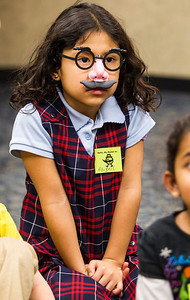 Kyle Grillot - kgrillot@shawmedia.com   Abigail Hori, 6, of Lake in the Hills listens while early literacy coordinator Dana Iaccino tells a story during the Mustache Mania early literacy event at the Algonquin Public Library Friday, February 28, 2014. The event, for children ages 4-6, features story telling, various crafts, mustache glasses, and playing with shaving cream.