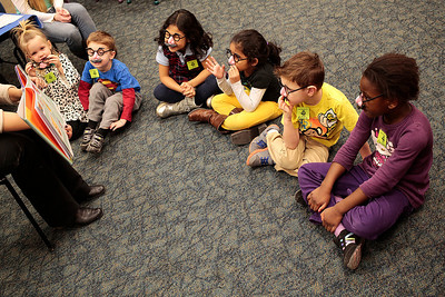 Kyle Grillot - kgrillot@shawmedia.com   Children listen while early literacy coordinator Dana Iaccino tells a story during the Mustache Mania early literacy event at the Algonquin Public Library Friday, February 28, 2014. The event, for children ages 4-6, features story telling, various crafts, mustache glasses, and playing with shaving cream.