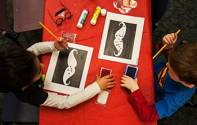 Kyle Grillot - kgrillot@shawmedia.com   Sruthi Guda, 5, (left) and Colin Boskey, 4, decorate mustache drawings during the Mustache Mania early literacy event at the Algonquin Public Library Friday, February 28, 2014. The event, for children ages 4-6, features story telling, various crafts, mustache glasses, and playing with shaving cream.