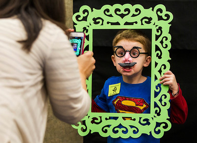 Kyle Grillot - kgrillot@shawmedia.com   Colin Boskey, 4, poses while early literacy coordinator Dana Iaccino takes his picture during the Mustache Mania early literacy event at the Algonquin Public Library Friday, February 28, 2014. The event, for children ages 4-6, features story telling, various crafts, mustache glasses, and playing with shaving cream.
