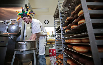 """Kyle Grillot - kgrillot@shawmedia.com   David McGrath of Crystal Lake works to keep up with the demand for Paczki in the kitchen of Country Doughnuts Tuesday, March 4, 2014. In the Midwest, Paczki Day is typically celebrated annually by immigrants and locals alike.""""We don't really have a heavily Polish population around here, there are a lot of Polish people in the county, but the people just like the extra rich product we're making for a couple days out of the year,"""" said co-owner Scott Offord. The shop has taken orders for 897 dozen paczki Tuesday and expects to reach 1000 as orders come in Wednesday."""
